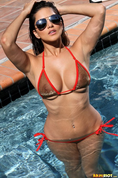 Sunny Leone's dark nipples are showing through her sheer wet bikini top.